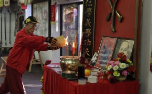Grandmaster Pui Chan lights incense and burns paper money to start the celebration